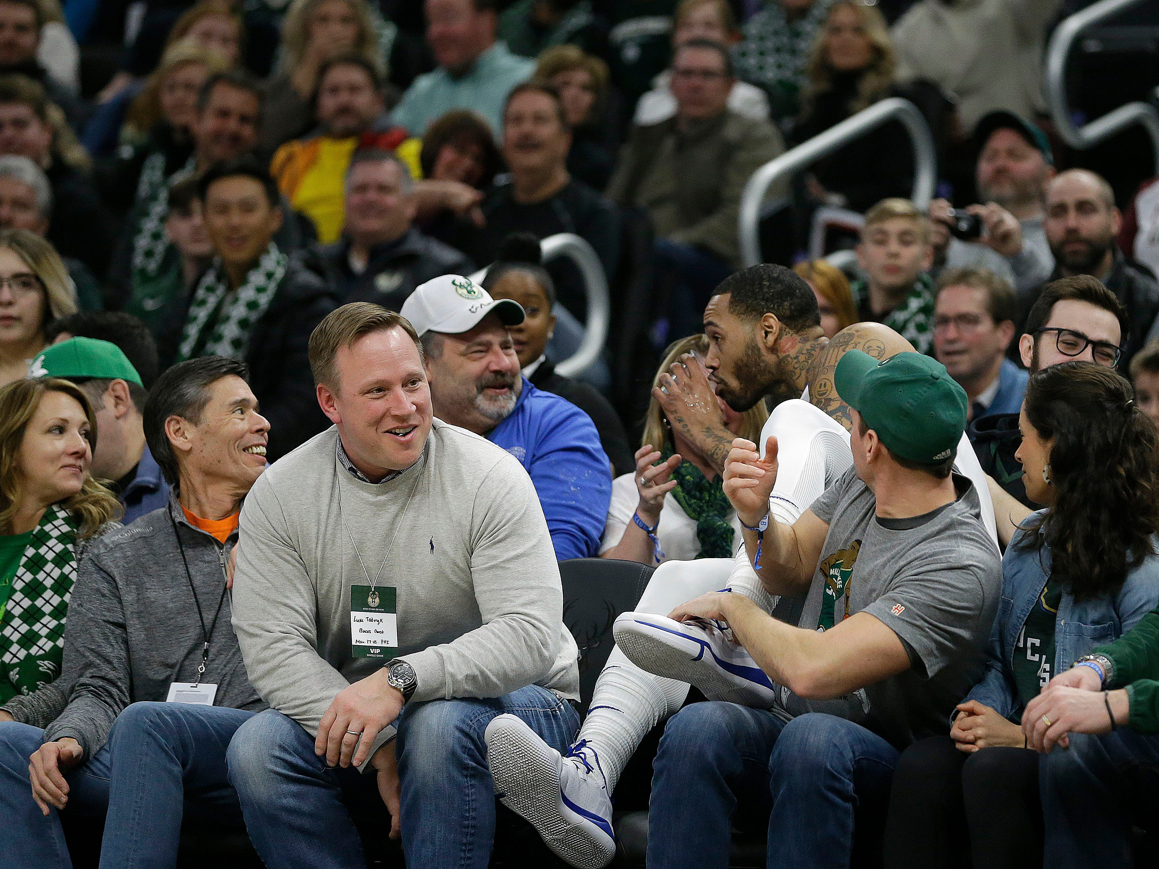 76ers forward Mike Scott takes a sip from a fan's drink after diving into the stands trying to save the ball from going out of bounds during the first half against the Bucks.