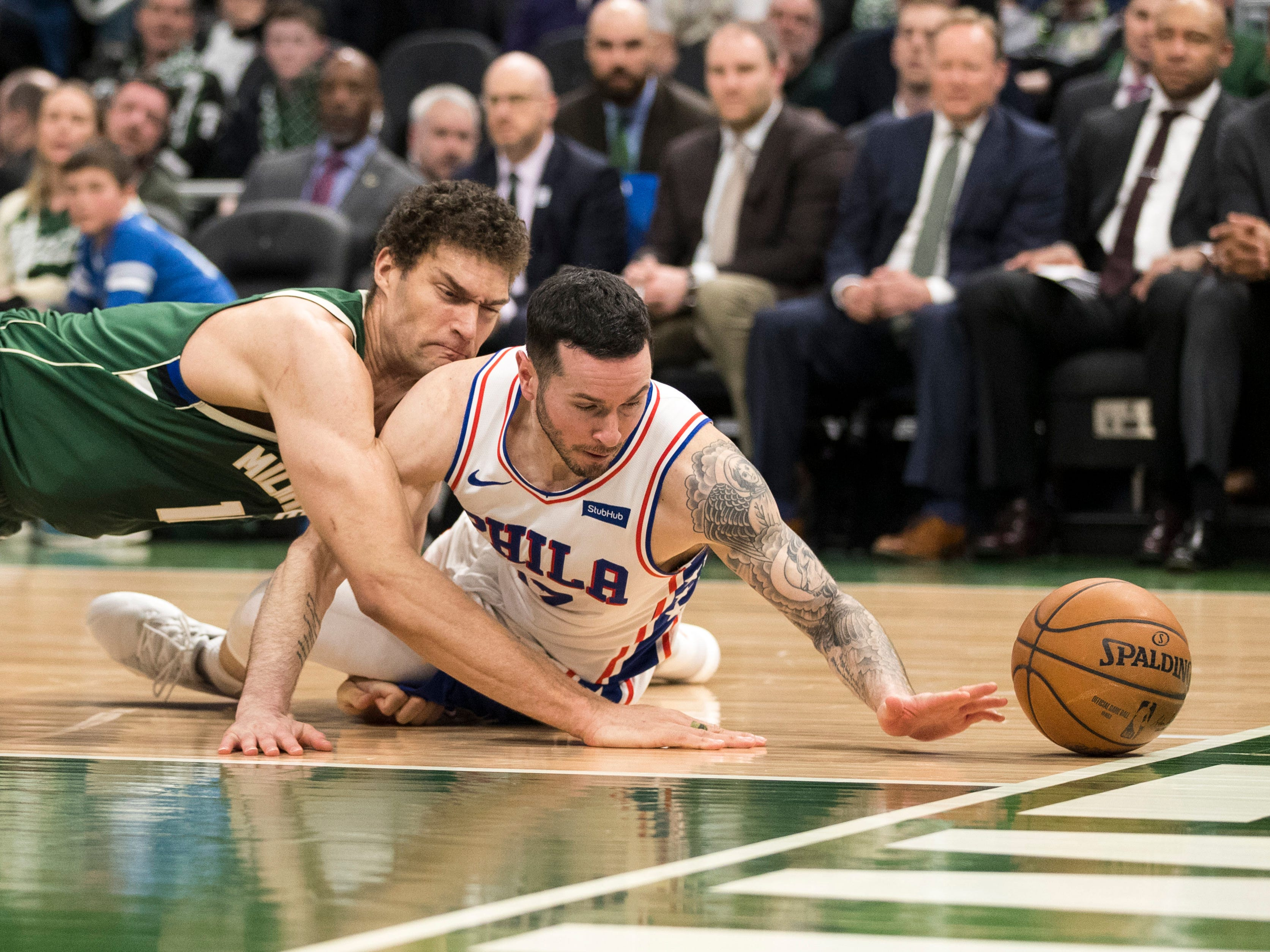 Bucks center Brook Lopez and 76ers guard JJ Redick reach for the loose ball during the fourth quarter.