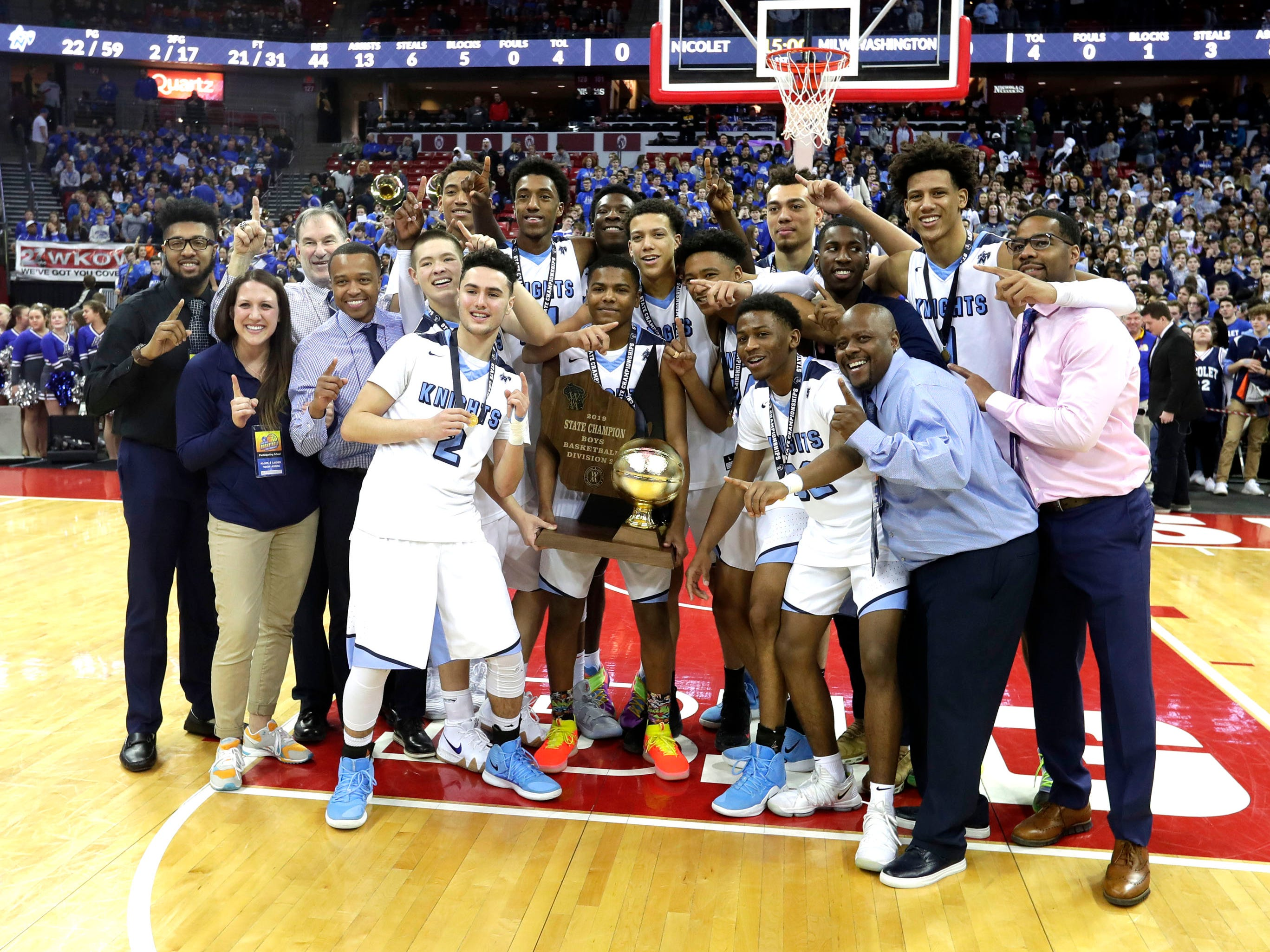 Nicolet players, coaches and support staff pose for photos with the Division 2 championship trophy after the Knights vanquished Milwaukee Washington, 67-54, in the WIAA state title game Saturday at the Kohl Center in Madison.