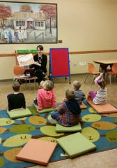 Tori Root reads to children during Story Time on Saturday at the Baxter County Library.
