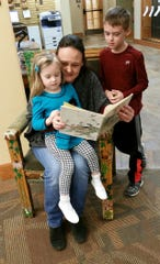 Tarra Simmons (center) is shown with her children Garnet (left) and Wave Simmons (standing) in the Reading Chair at the Baxter County Library