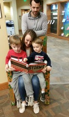 Dr. Matt Dover (standing) and his wife, Cynthia, are shown with their children Luke and Jackson in the Reading Chair at the Baxter County Library.