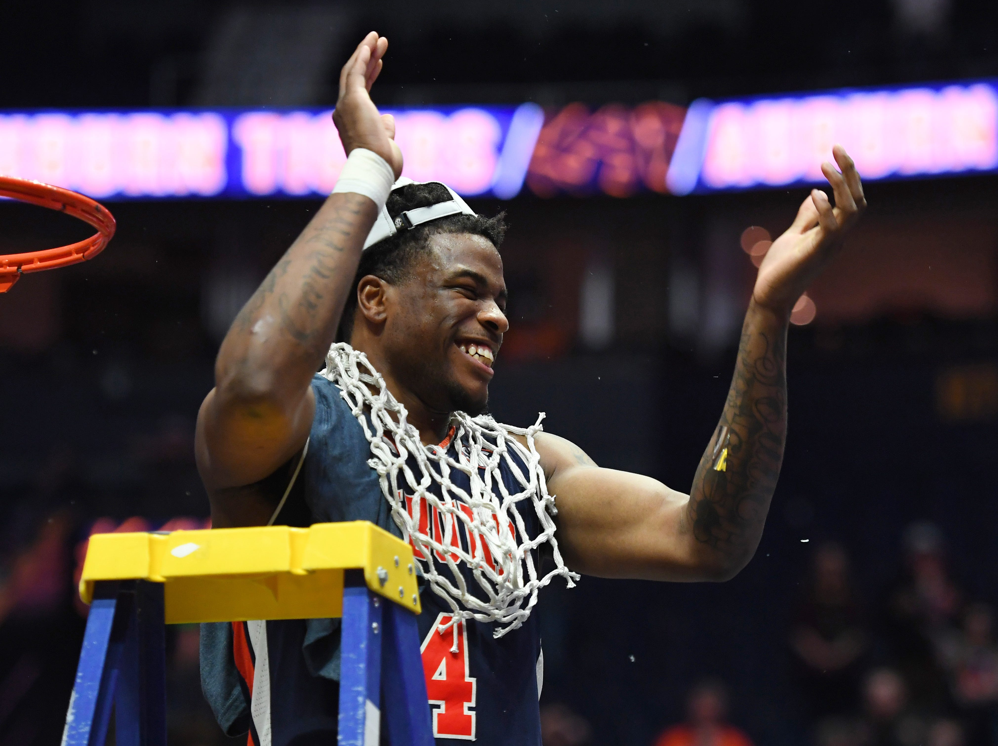 Mar 17, 2019; Nashville, TN, USA; Auburn Tigers guard Malik Dunbar (4) celebrates as he cuts down the nets after beating the Tennessee Volunteers in the SEC conference tournament championship game at Bridgestone Arena. Mandatory Credit: Christopher Hanewinckel-USA TODAY Sports