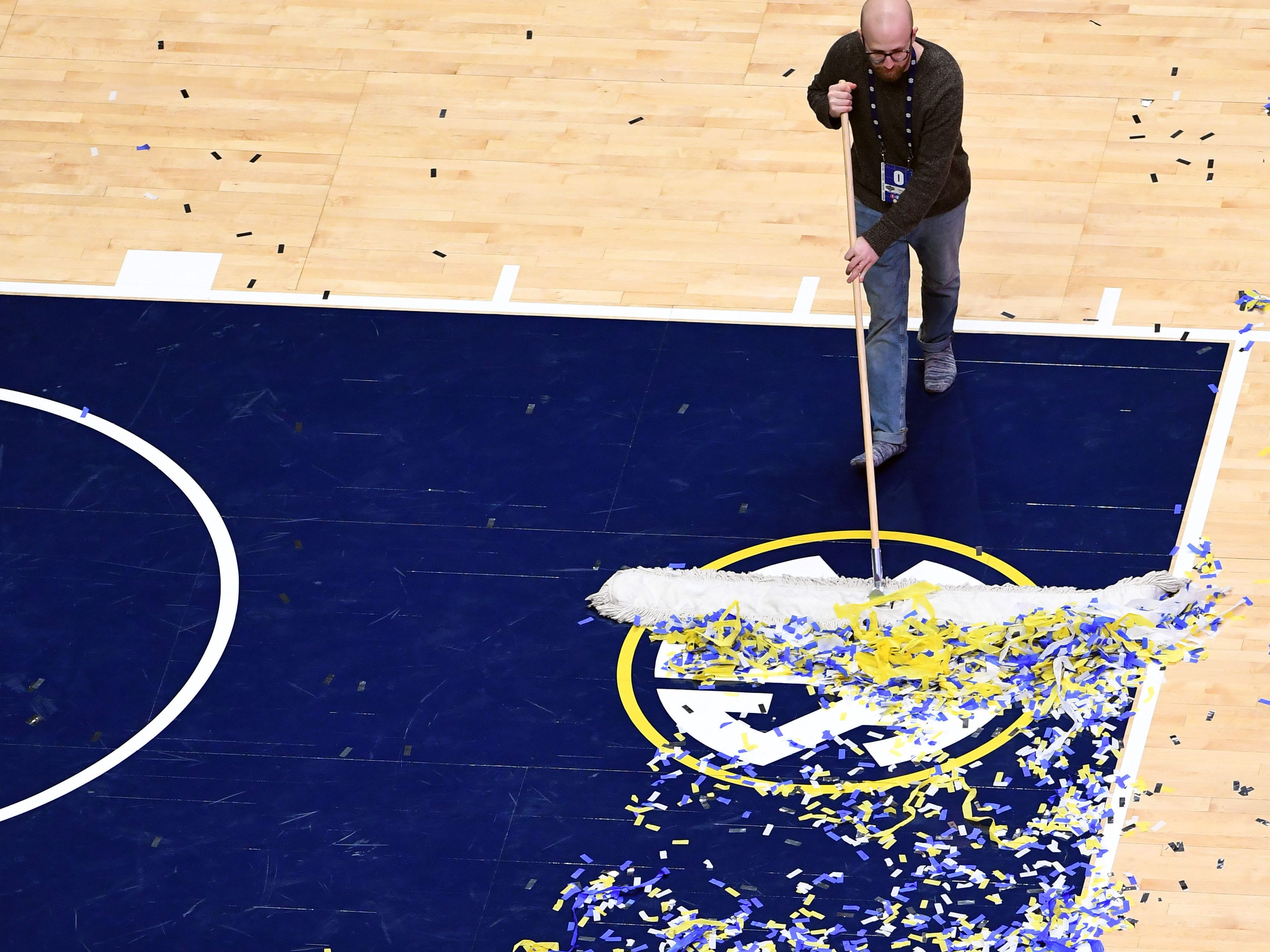 Mar 17, 2019; Nashville, TN, USA; A member of the Bridgestone Arena crew sweeps confetti off the court after a win by the Auburn Tigers over the Tennessee Volunteers in the SEC conference tournament championship game at Bridgestone Arena. Mandatory Credit: Christopher Hanewinckel-USA TODAY Sports
