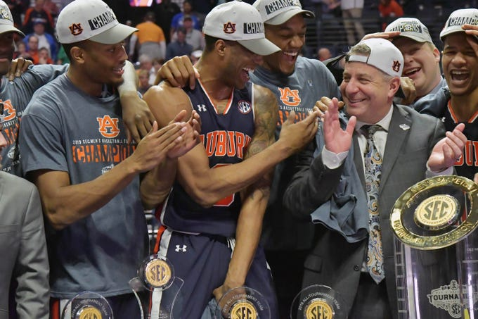 Mar 17, 2019; Nashville, TN, USA; Auburn Tigers head coach Bruce Pearl reacts with Auburn forward Horace Spencer (0) and his teammates as his hat is reversed by the team following the championship game between the Tennessee Volunteers and the Auburn Tigers  in the SEC conference tournament at Bridgestone Arena. Auburn won 84-64. Mandatory Credit: Jim Brown-USA TODAY Sports
