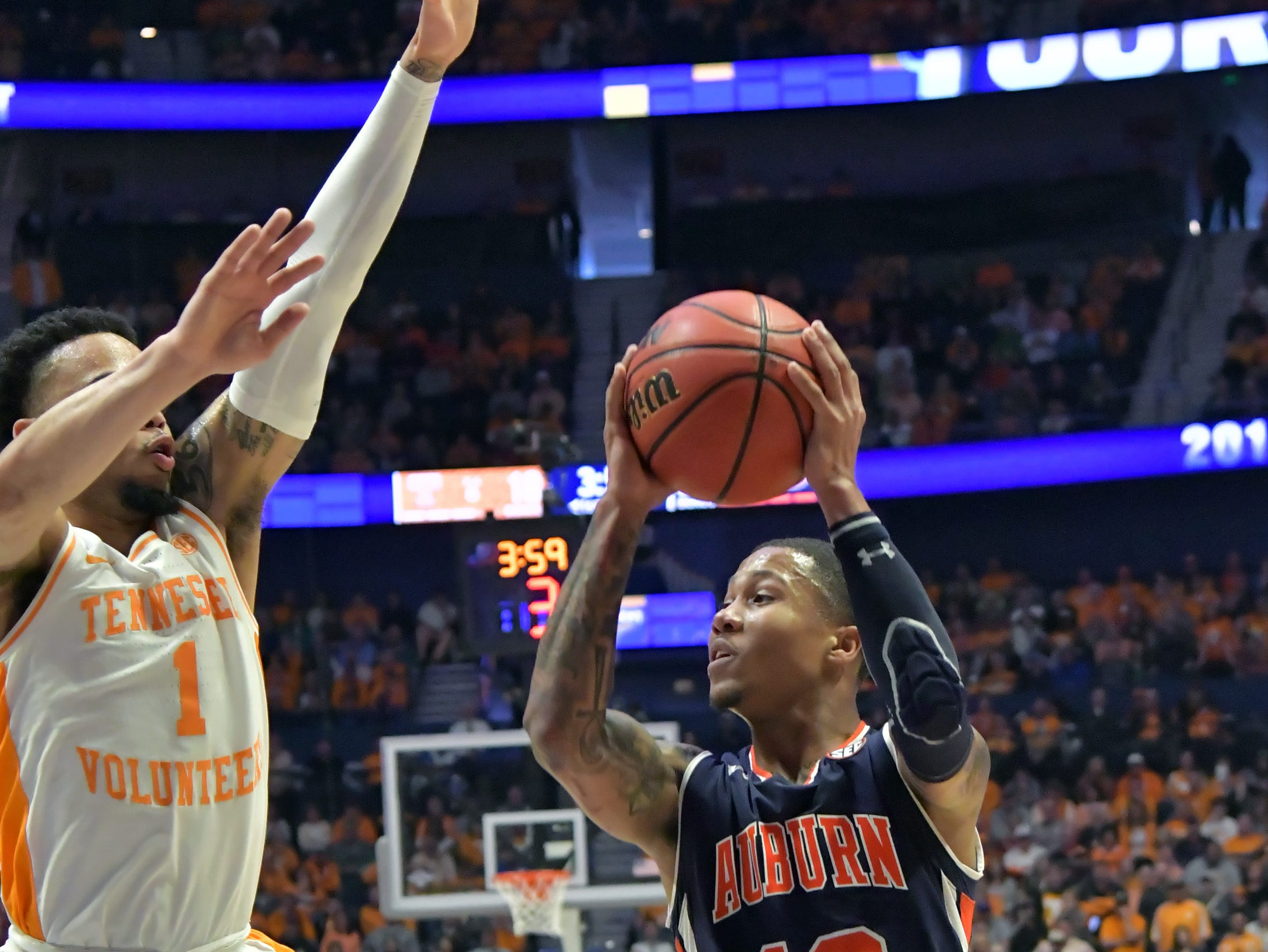 Mar 17, 2019; Nashville, TN, USA; Auburn Tigers guard J'Von McCormick (12) passes againstTennessee Volunteers guard Lamonte Turner (1) during the first half of the championship game in the SEC conference tournament at Bridgestone Arena. Mandatory Credit: Jim Brown-USA TODAY Sports