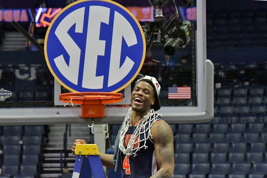Mar 17, 2019; Nashville, TN, USA; Auburn Tigers guard Malik Dunbar (4) reacts after making the final cut on the net an placing it around his neck following the championship game between the Tennessee Volunteers and the Auburn Tigers  in the SEC conference tournament at Bridgestone Arena. Auburn won 84-64. Mandatory Credit: Jim Brown-USA TODAY Sports