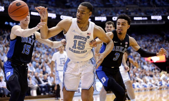 North Carolina's Garrison Brooks (15) reaches for the ball against Duke's Alex O'Connell (15) and Tre Jones (3) during the first half of an NCAA college basketball game in Chapel Hill, N.C., Saturday, March 9, 2019. (AP Photo/Gerry Broome)
