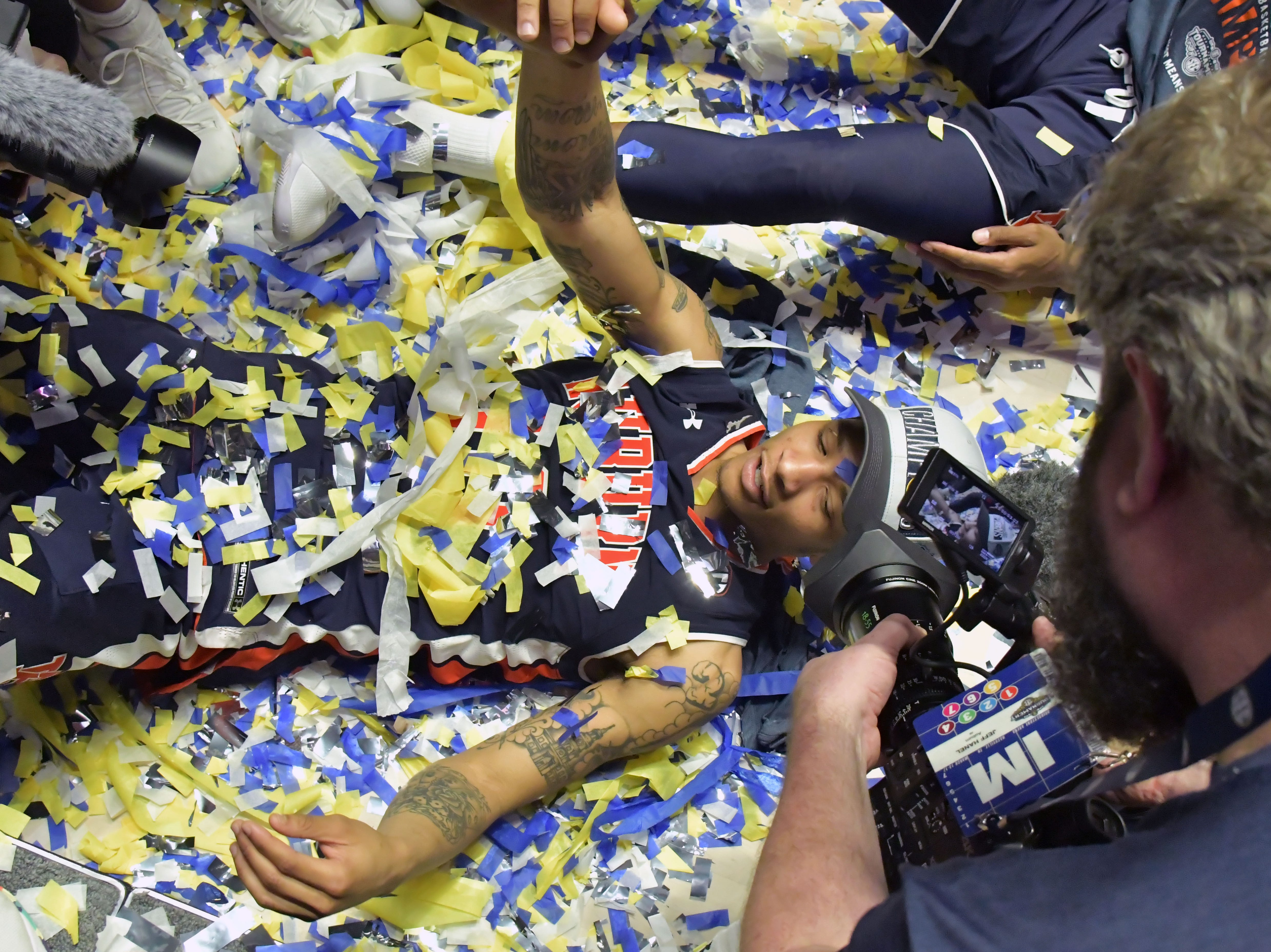 Mar 17, 2019; Nashville, TN, USA; Auburn Tigers guard Samir Doughty (10) is covered in confetti as he lies on the playing floor following the championship game between the Tennessee Volunteers and the Auburn Tigers  in the SEC conference tournament at Bridgestone Arena. Auburn won 84-64. Mandatory Credit: Jim Brown-USA TODAY Sports