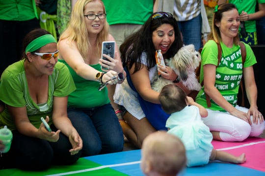 Ingrid Fuller, second from right, encourages her daughter Shelby Fuller, 14 months, to crawl over the finish line during the Baby Leprechaun Races at Miromar Outlets in Estero on Sunday, March 17, 2019. Shelby won her heat and came in second in the final.