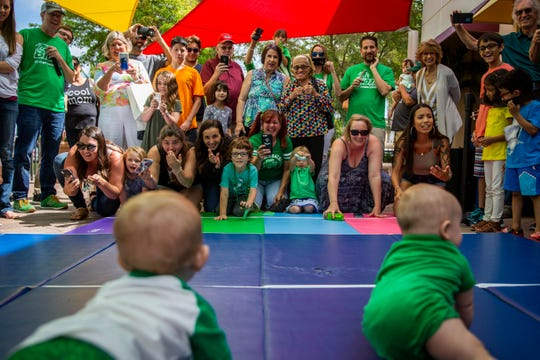 Family members cheer as they try to encourage their babies to crawl during the Baby Leprechaun Races at Miromar Outlets in Estero on Sunday, March 17, 2019.