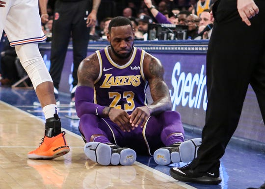Los Angeles Lakers forward LeBron James (23) sits on the court after getting fouled in the second quarter against the New York Knicks at Madison Square Garden.