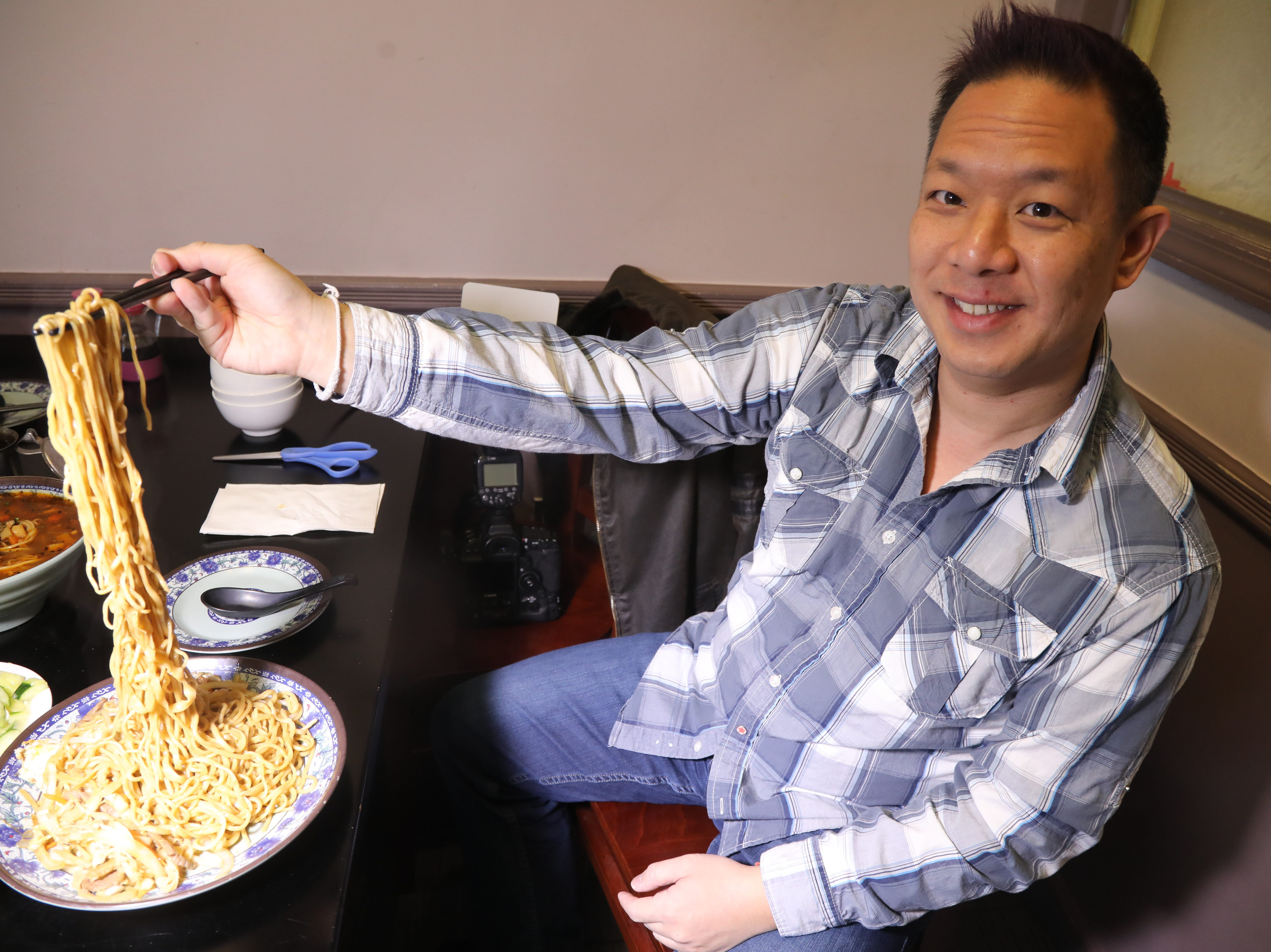 Our guide food blogger Danny Chin with long hand made noodles that are cut with scissors from Shan Shan Noodles.