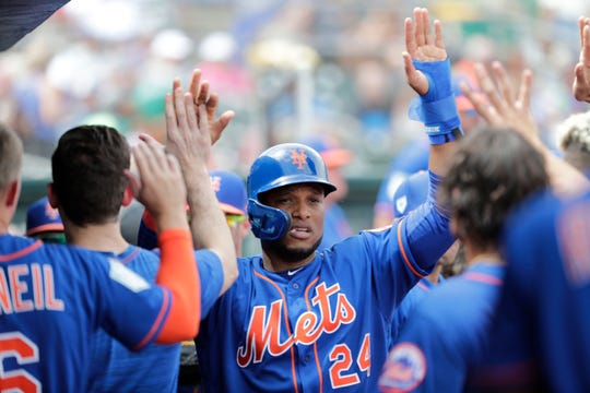 New York Mets' Robinson Cano (24) celebrates with his teammates in the dugout after scoring in the third during an exhibition spring training baseball game against the Miami Marlins, Saturday, March 16, 2019, in Jupiter, Fla.