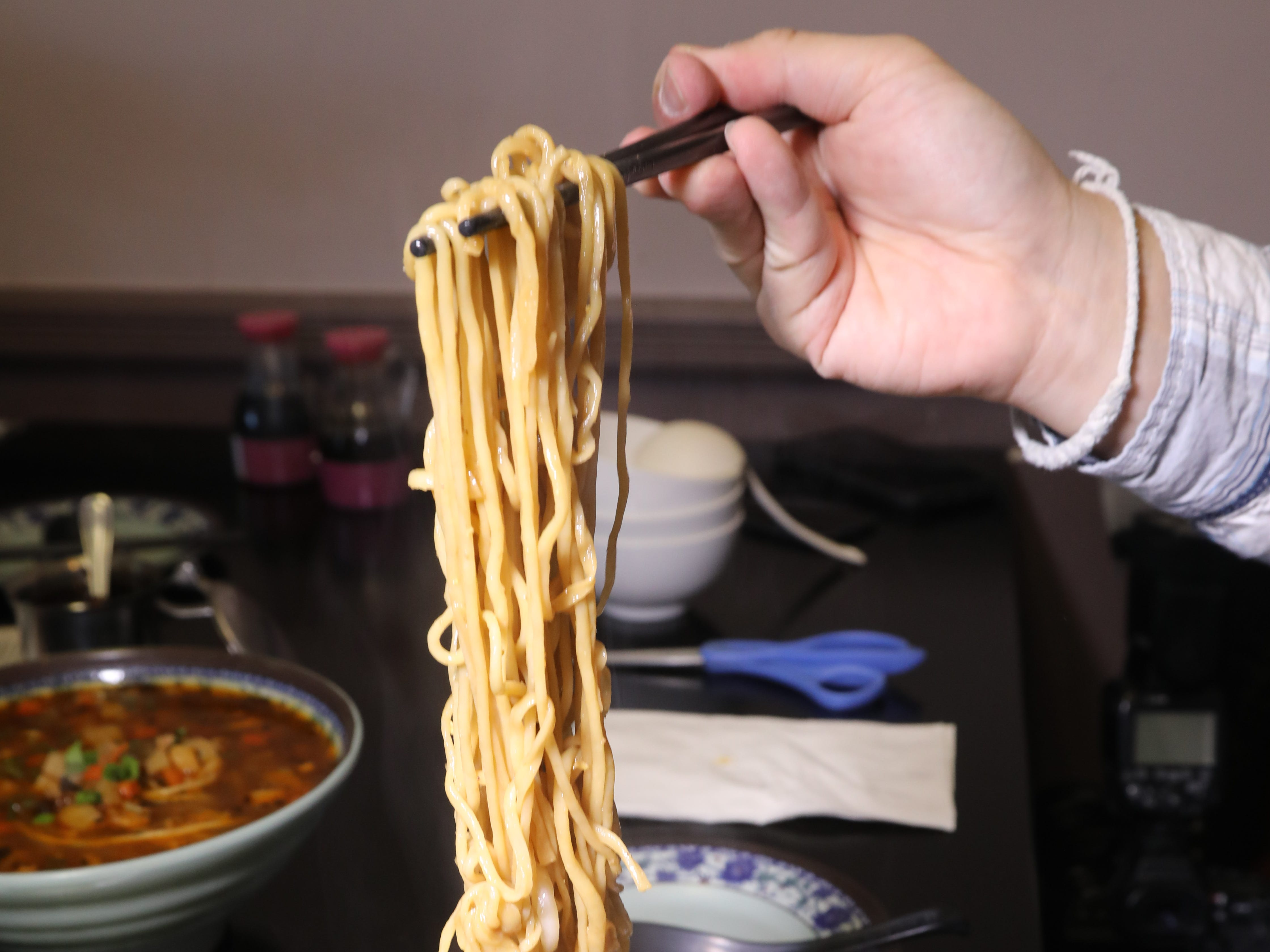 Long hand made noodles that are cut with scissors from Shan Shan Noodles.