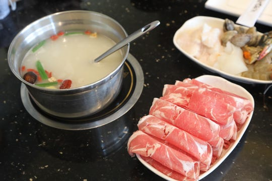 Broth is heated on an element at the dining table where large selections of meats, vegetables and seafood are cooked at V-Yan Hotpot and BBQ.
