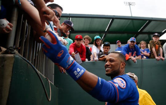 New York Mets' Robinson Cano (24) signs baseballs before an exhibition spring training baseball game against the Miami Marlins on Saturday, March 16, 2019, in Jupiter, Fla.