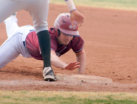 Junior Wildcat Fernie Munoz dives safely back to first base on a Miyamura pick-off attempt.