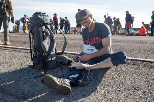 Jay Ware from Colorado Springs stops near mile 8 to patch up some developing blisters. Ware participated in the Bataan Memorial Death March for the first time on Sunday, March 17, 2019, and said the weight of the pack was more of a challenge than he anticipated.