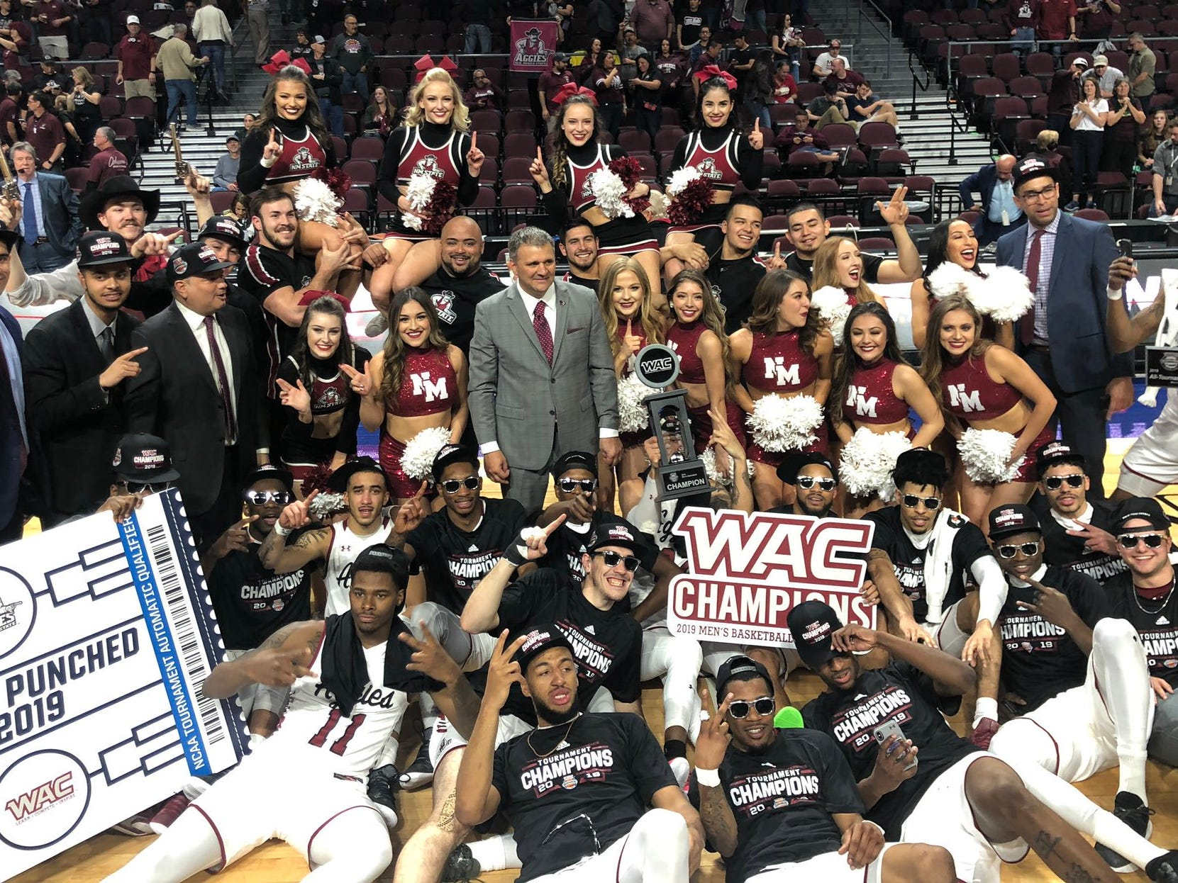 The New Mexico State men's basketball team gathers with the WAC trophy after winning the 2019 WAC Tournament title on Saturday, March 16, 2019, in Las Vegas.