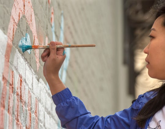 Veronique Zayas, owner of HatchMark Studio and Somi Choi, lead designer at idgroup, work on a community-inspired mural on the building housing Zarzaur Law Firm Sunday, March 17, 2019. The two invited downtown businesses to submit an application for them to come out and paint the mural and Zarzaur was chosen.