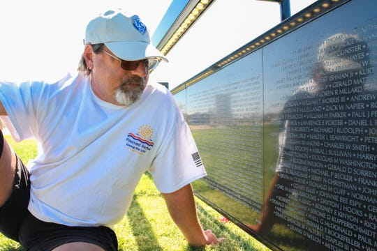 George Ballman looks at the name of his fallen friend at a traveling replica of the Vietnam Veterans Memorial at Pleasant Harbor at Lake Pleasant in Peoria on March 16, 2019.