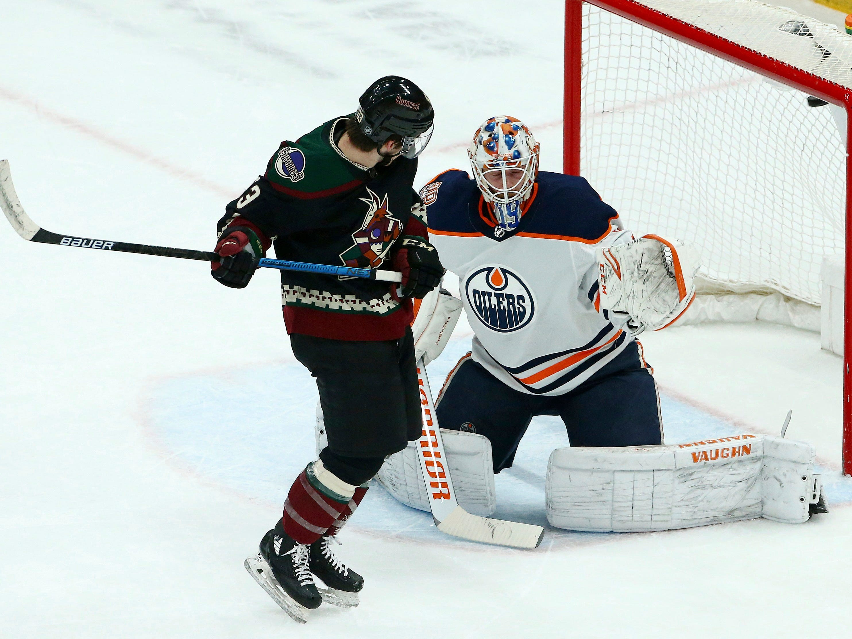 Arizona Coyotes right wing Conor Garland, left, sets a screen as Edmonton Oilers goaltender Mikko Koskinen, right, gives up a goal to Coyotes' Alex Galchenyuk during the first period of an NHL hockey game Saturday, March 16, 2019, in Glendale, Ariz.