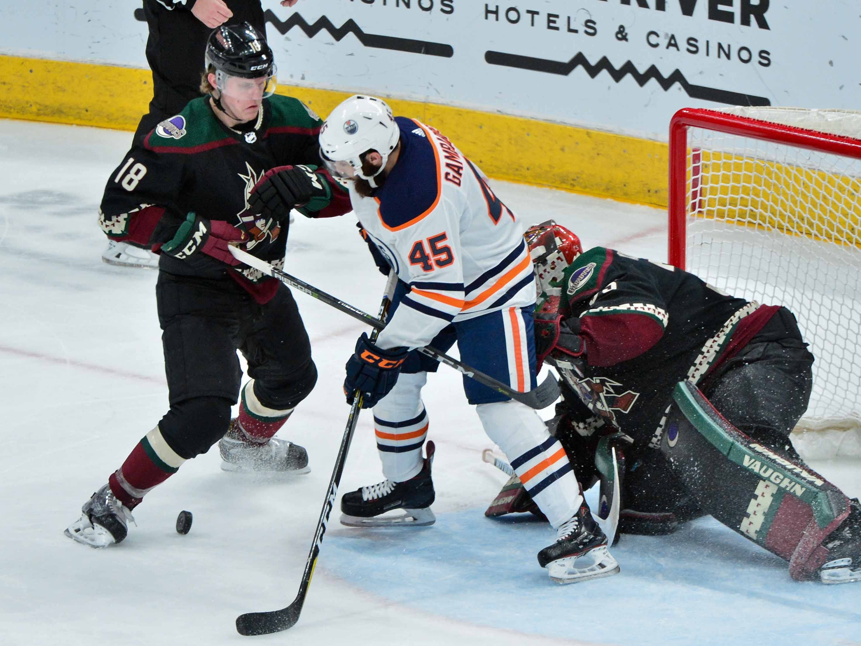 Mar 16, 2019; Glendale, AZ, USA; Arizona Coyotes center Christian Dvorak (18) and Edmonton Oilers center Joe Gambardella (45) battle for the puck during the second period at Gila River Arena.