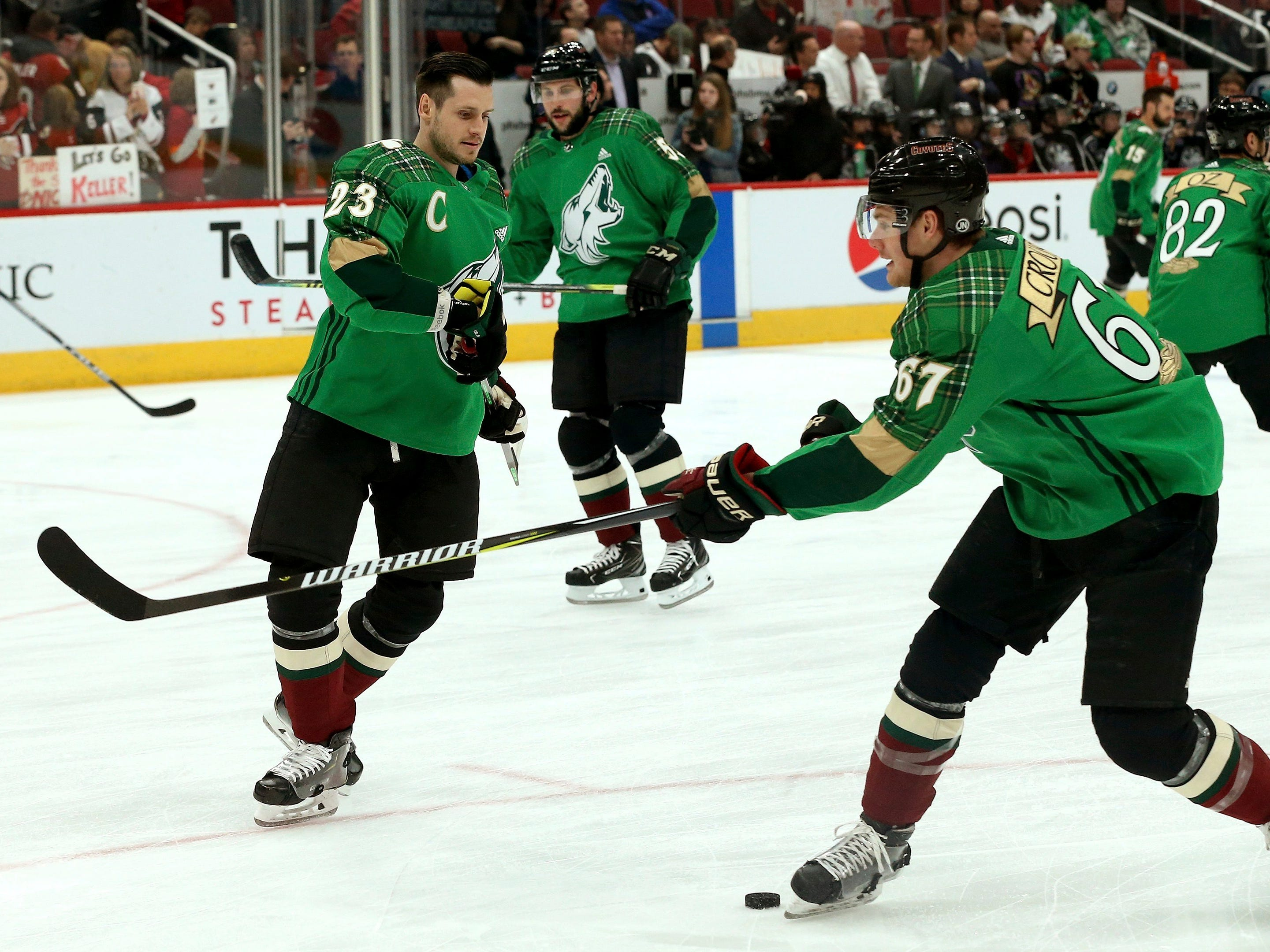 Arizona Coyotes' Lawson Crouse (67) fires a practice shot past Oliver Ekman-Larsson (23) as the entire team sports St. Patrick's Day green uniform tops prior to an NHL hockey game against the Edmonton Oilers Saturday, March 16, 2019, in Glendale, Ariz.