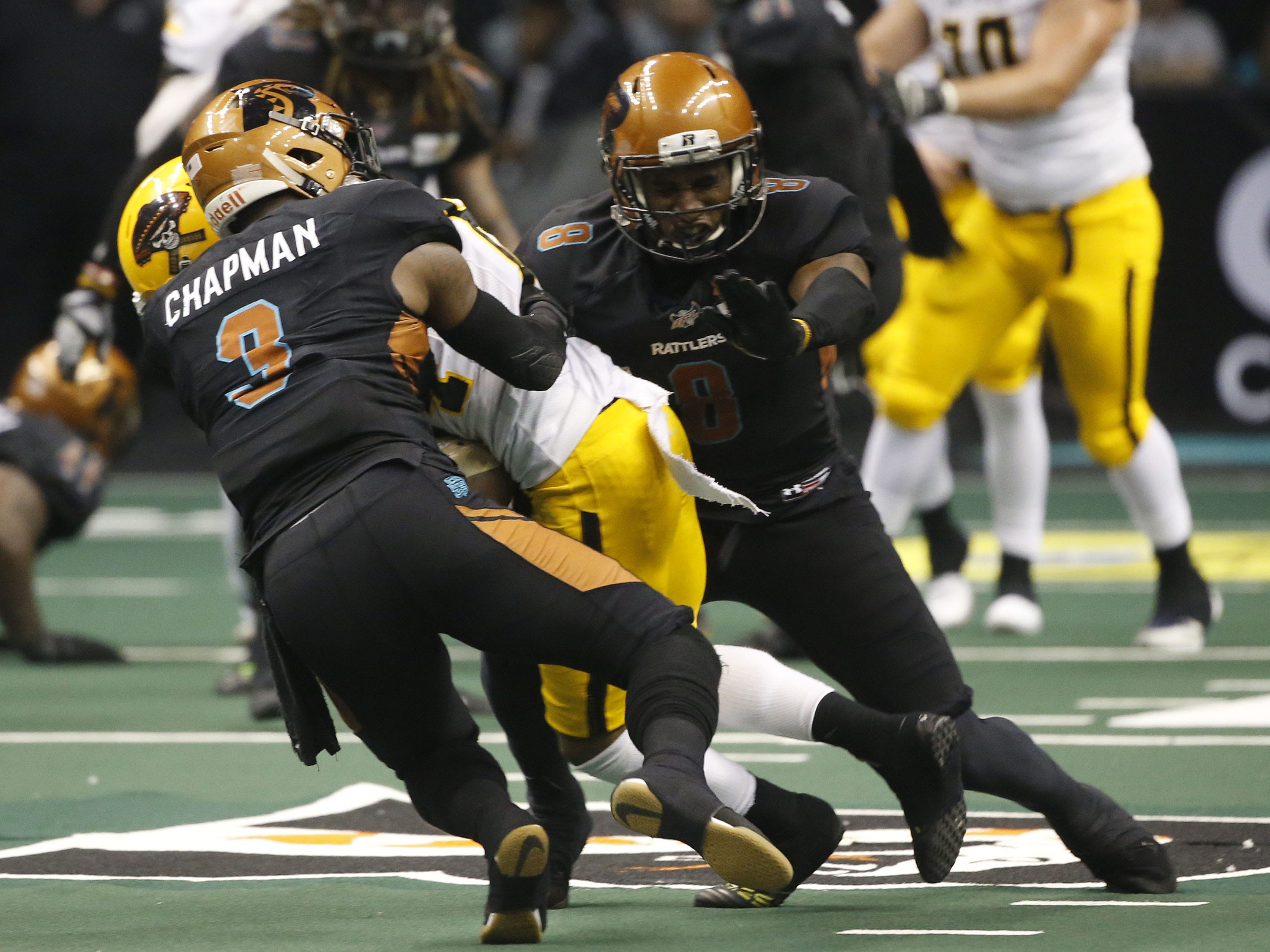 Rattlers' Allen Chapman (3) and Davontae Merriweather (8) tackle Sugar Skulls' Donovan Rasberry (84) during the second half at Talking Stick Resort Arena in Phoenix, Ariz. on March 16, 2019.