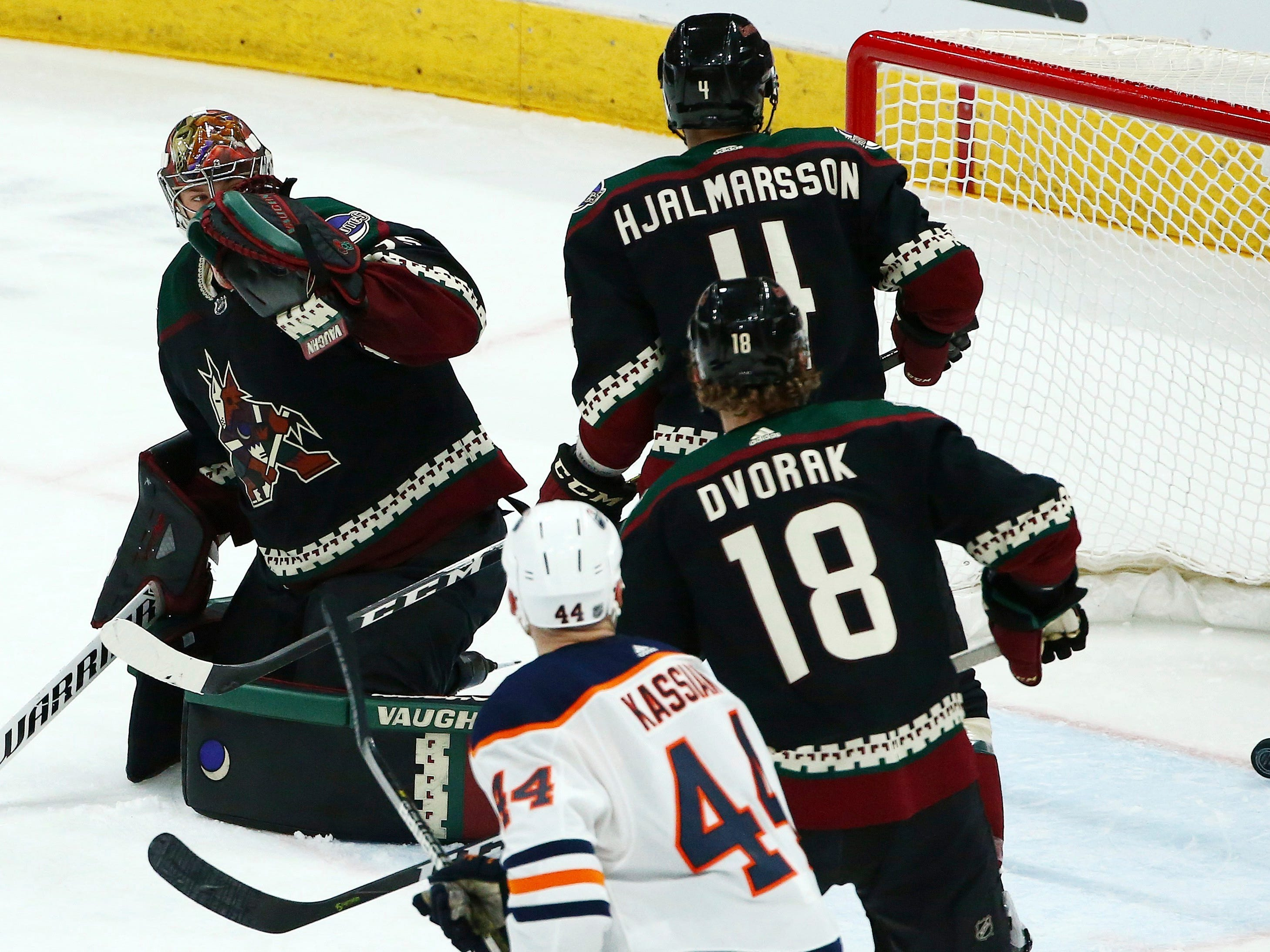 Arizona Coyotes goaltender Darcy Kuemper, left, gives up a goal to Edmonton Oilers' Matt Benning as Coyotes defenseman Niklas Hjalmarsson (4) and center Christian Dvorak (18) and Oilers right wing Zack Kassian (44) skate nearby during the second period of an NHL hockey game Saturday, March 16, 2019, in Glendale, Ariz.