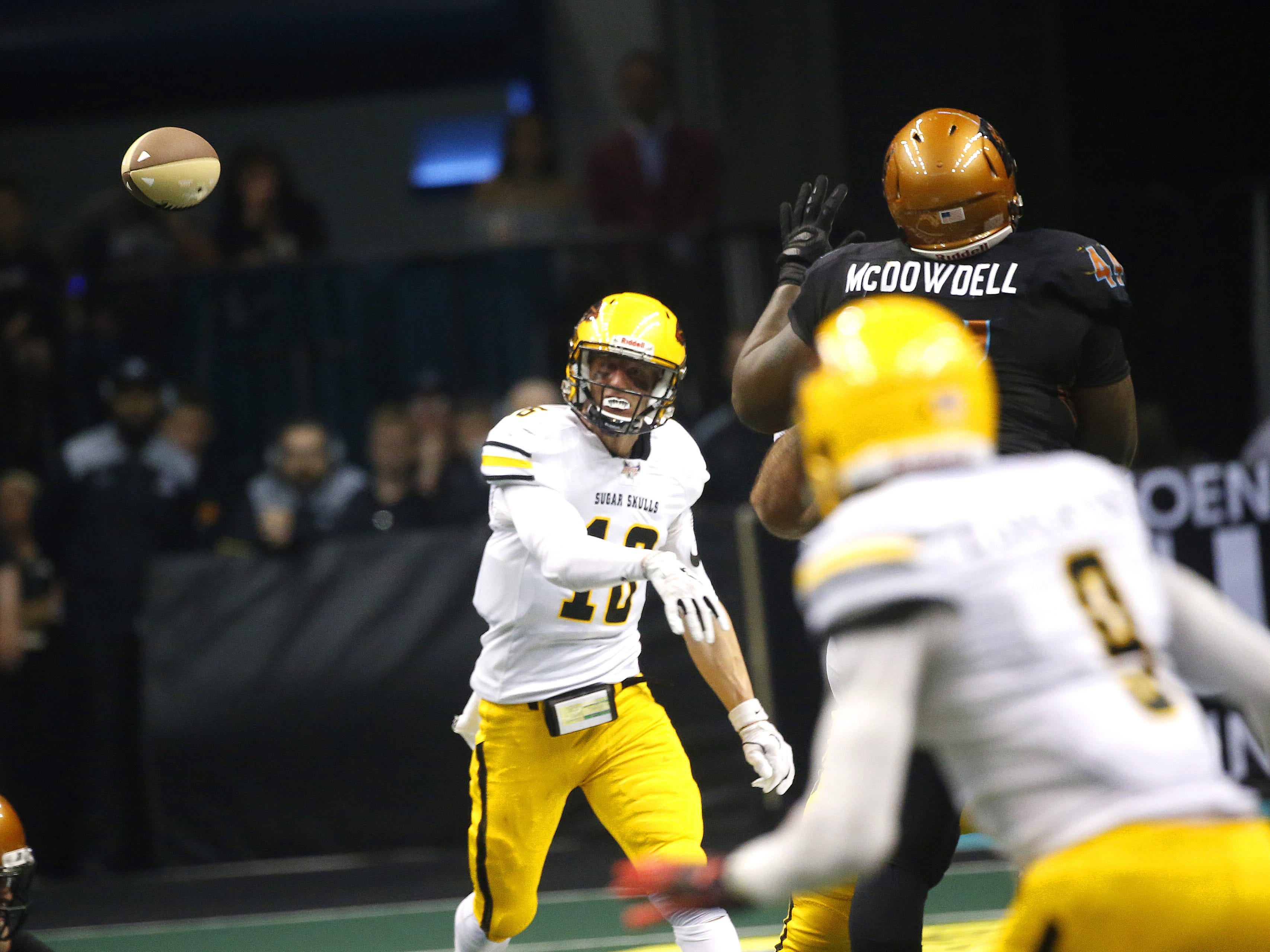 Sugar Skulls' Matt Behrendt (16) throws a pass against the rush of Rattlers' Lance McDowdell (44) during the first half at Talking Stick Resort Arena in Phoenix, Ariz. on March 16, 2019.