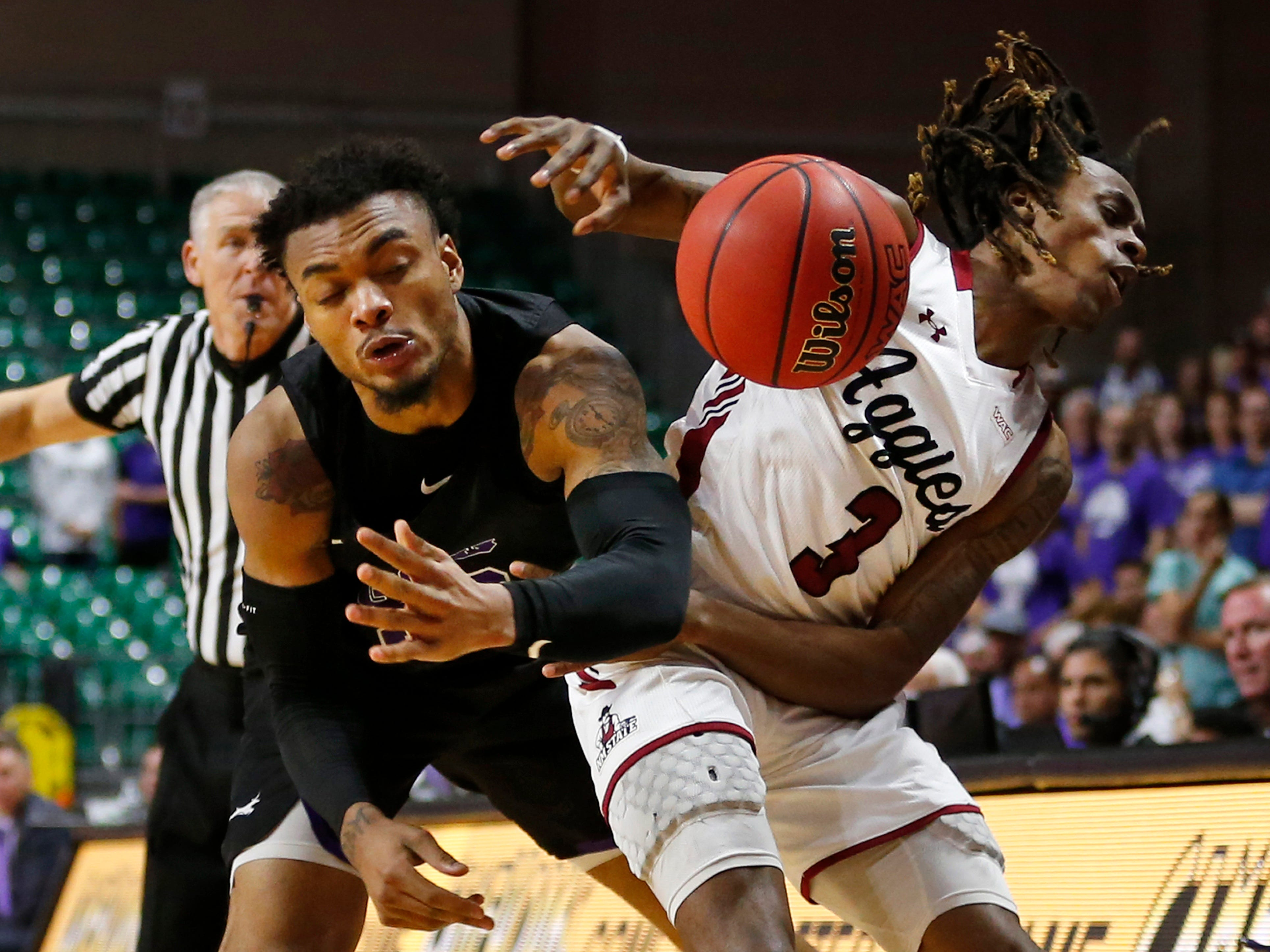 Grand Canyon's Carlos Johnson, left, fouls New Mexico State guard Terrell Brown as he tries to pick off a pass during an NCAA college basketball game for the Western Athletic Conference men's tournament championship Saturday, March 16, 2019, in Las Vegas.