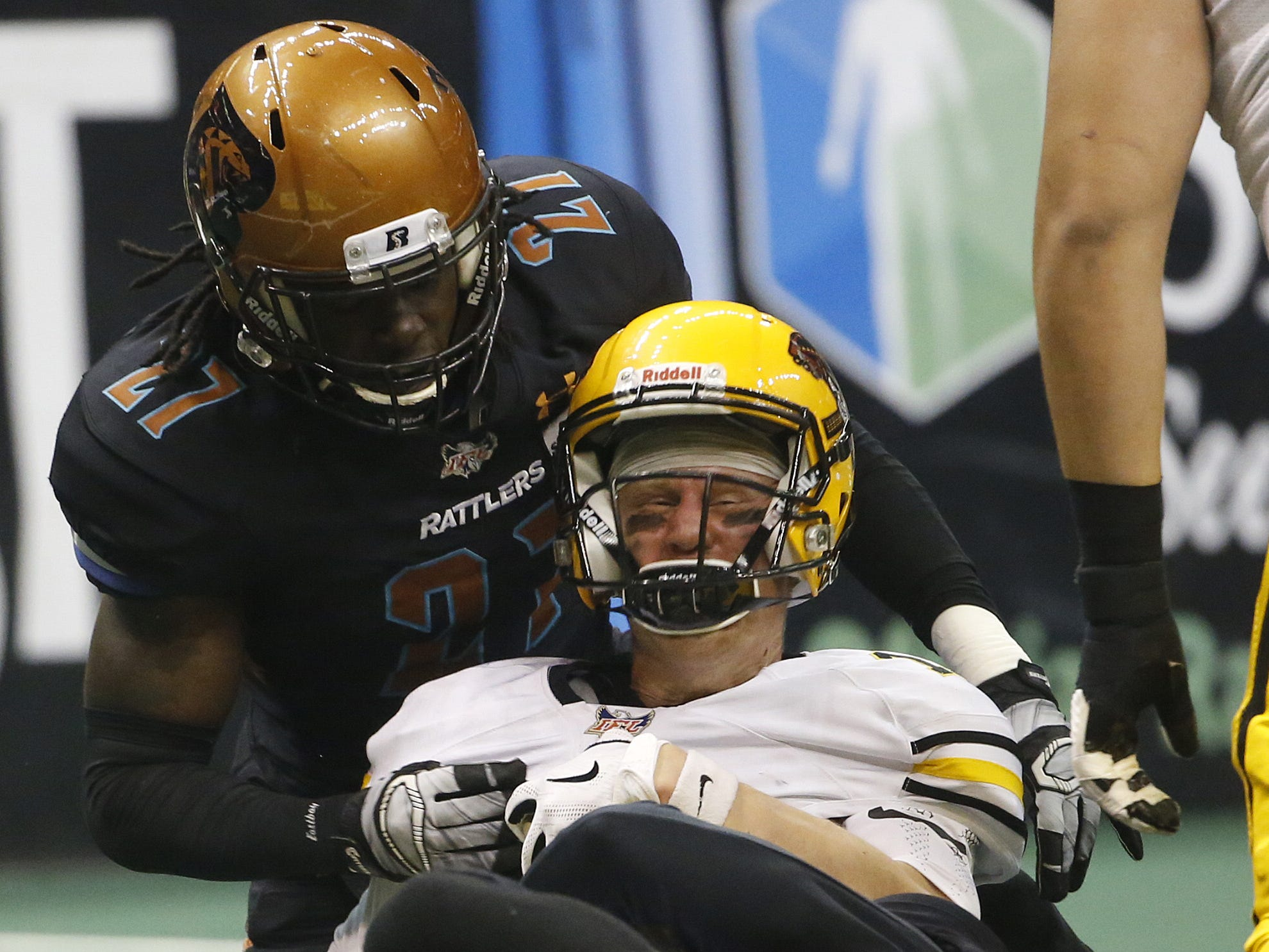 Rattlers' Dillon Winfrey (15) and and Devin Cockrell (27) tackle Sugar Skulls quarterback Matt Behrendt (16) during the first half at Talking Stick Resort Arena in Phoenix, Ariz. on March 16, 2019.