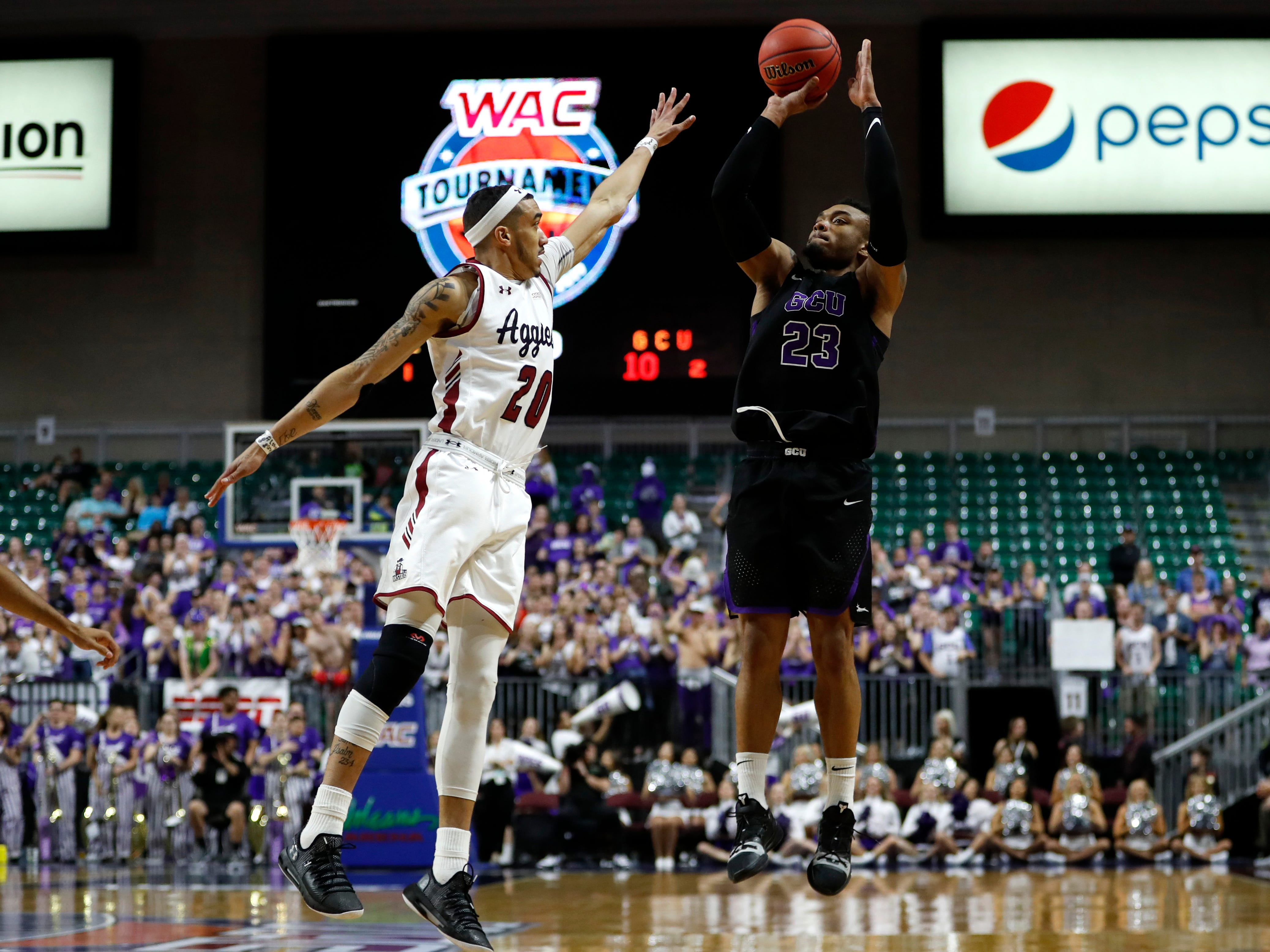 Grand Canyon's Carlos Johnson (23) shoots over New Mexico State guard Trevelin Queen (20) during an NCAA college basketball game for the Western Athletic Conference men's tournament championship Saturday, March 16, 2019, in Las Vegas.