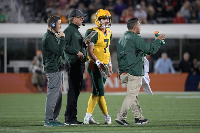 Arizona Hotshots head coach Rick Neuheisel, second from left, talks with quarterback John Wolford (7) during the first half of an AAF football game against the Orlando Apollos Saturday, March 16, 2019, in Orlando, Fla.
