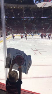 Trever London, 6, holds up a target during warmups prior to a recent Coyotes game at Gila River Arena.