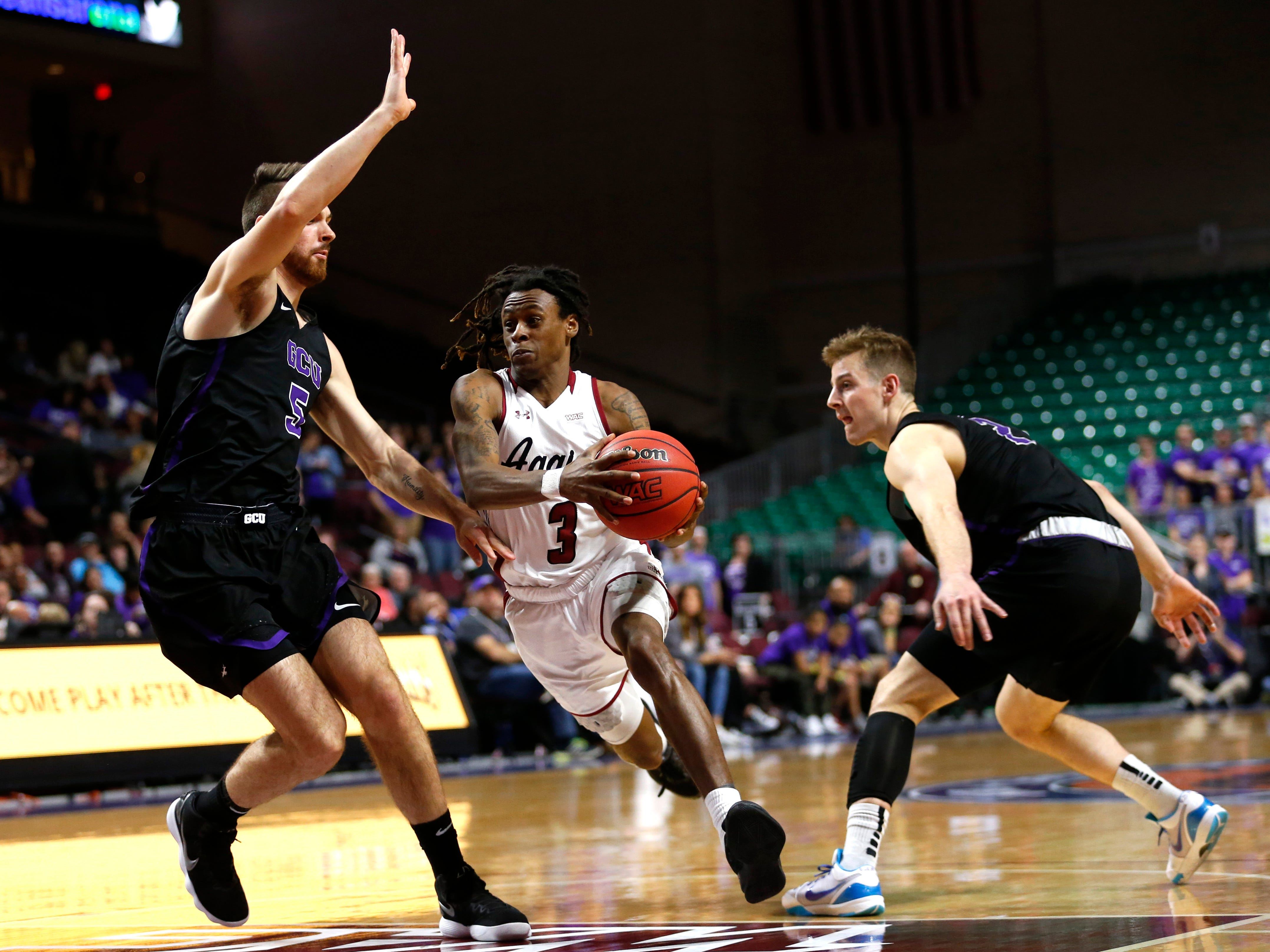 New Mexico State guard Terrell Brown (3) drives by Grand Canyon's Matt Jackson (5) and Trey Drechsel (2) during an NCAA college basketball game for the Western Athletic Conference men's tournament championship Saturday, March 16, 2019, in Las Vegas. New Mexico State won 89-57.