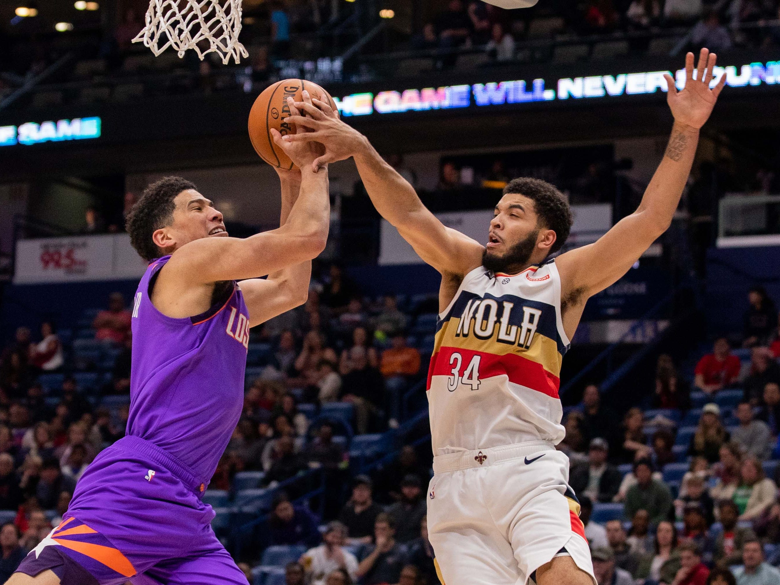 Mar 16, 2019; New Orleans, LA, USA; Phoenix Suns guard Devin Booker (1) is fouled going to the basket by New Orleans Pelicans guard Kenrich Williams (34) during the first half at Smoothie King Center.