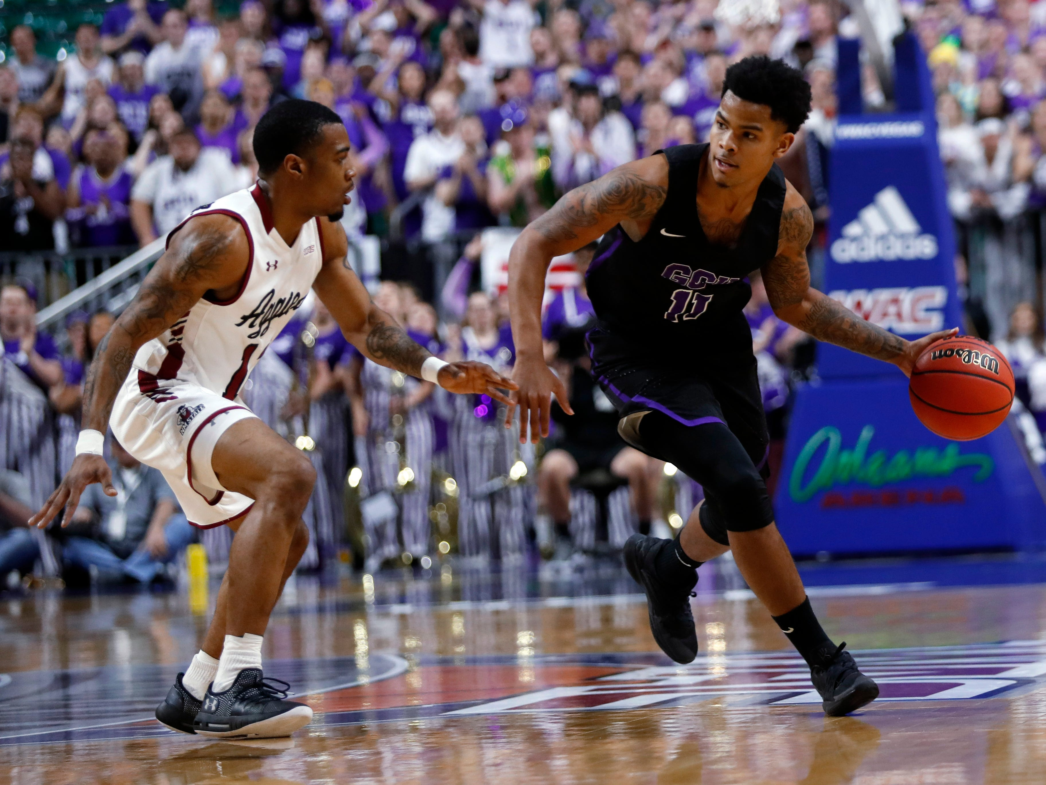 Grand Canyon's Damari Mislead (11) drives by New Mexico State guard AJ Harris (12) during the first half of an NCAA college basketball game for the Western Athletic Conference men's tournament championship Saturday, March 16, 2019, in Las Vegas.