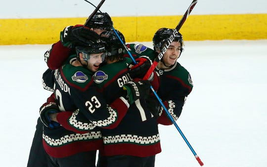 Arizona Coyotes center Alex Galchenyuk, back to camera, celebrates his goal against the Edmonton Oilers with defenseman Oliver Ekman-Larsson (23), defenseman Jakob Chychrun (6) and center Clayton Keller, right, during the first period of an NHL hockey game Saturday, March 16, 2019, in Glendale, Ariz.