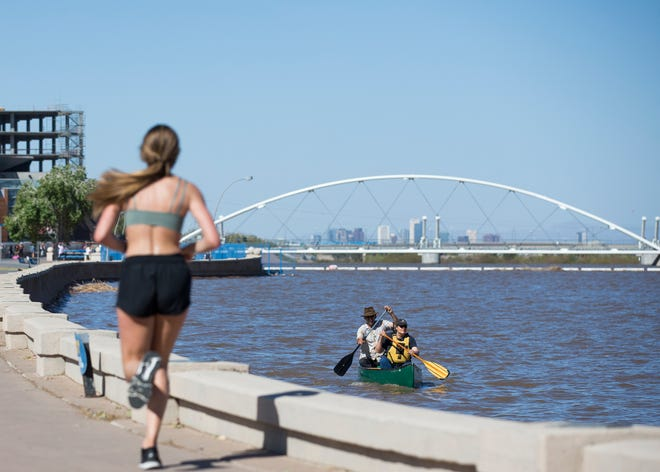 Robert Drummer (left, paddling back of canoe) and Diane Laush (right, paddling front) enjoy a weekend of warm weather at Tempe Town Lake in Tempe, Ariz., on Saturday, March 16, 2019.