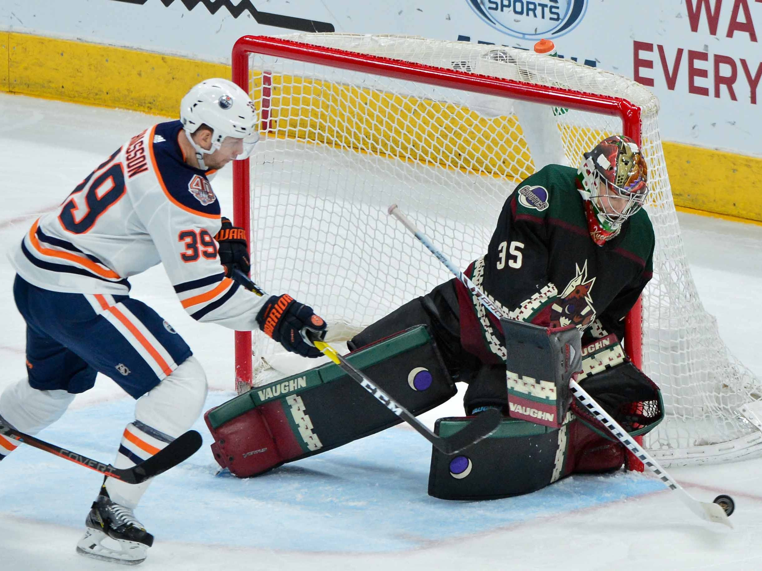 Mar 16, 2019; Glendale, AZ, USA; Arizona Coyotes goaltender Darcy Kuemper (35) sweeps the puck away from Edmonton Oilers right wing Alex Chiasson (39) during the second period at Gila River Arena.