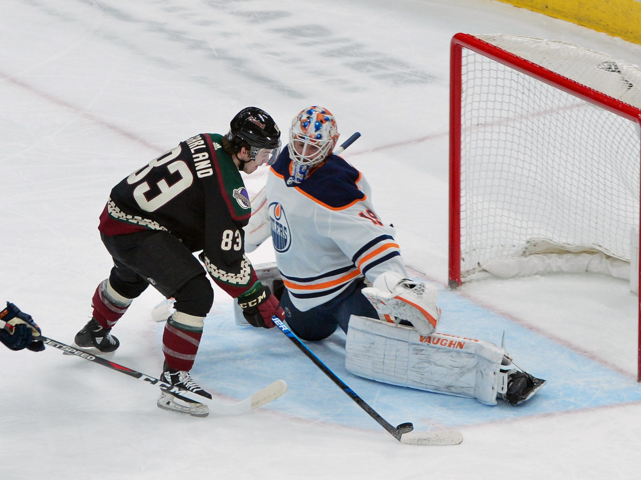 Mar 16, 2019; Glendale, AZ, USA; Edmonton Oilers goaltender Mikko Koskinen (19) makes a save against Arizona Coyotes right wing Conor Garland (83) during the first period at Gila River Arena.
