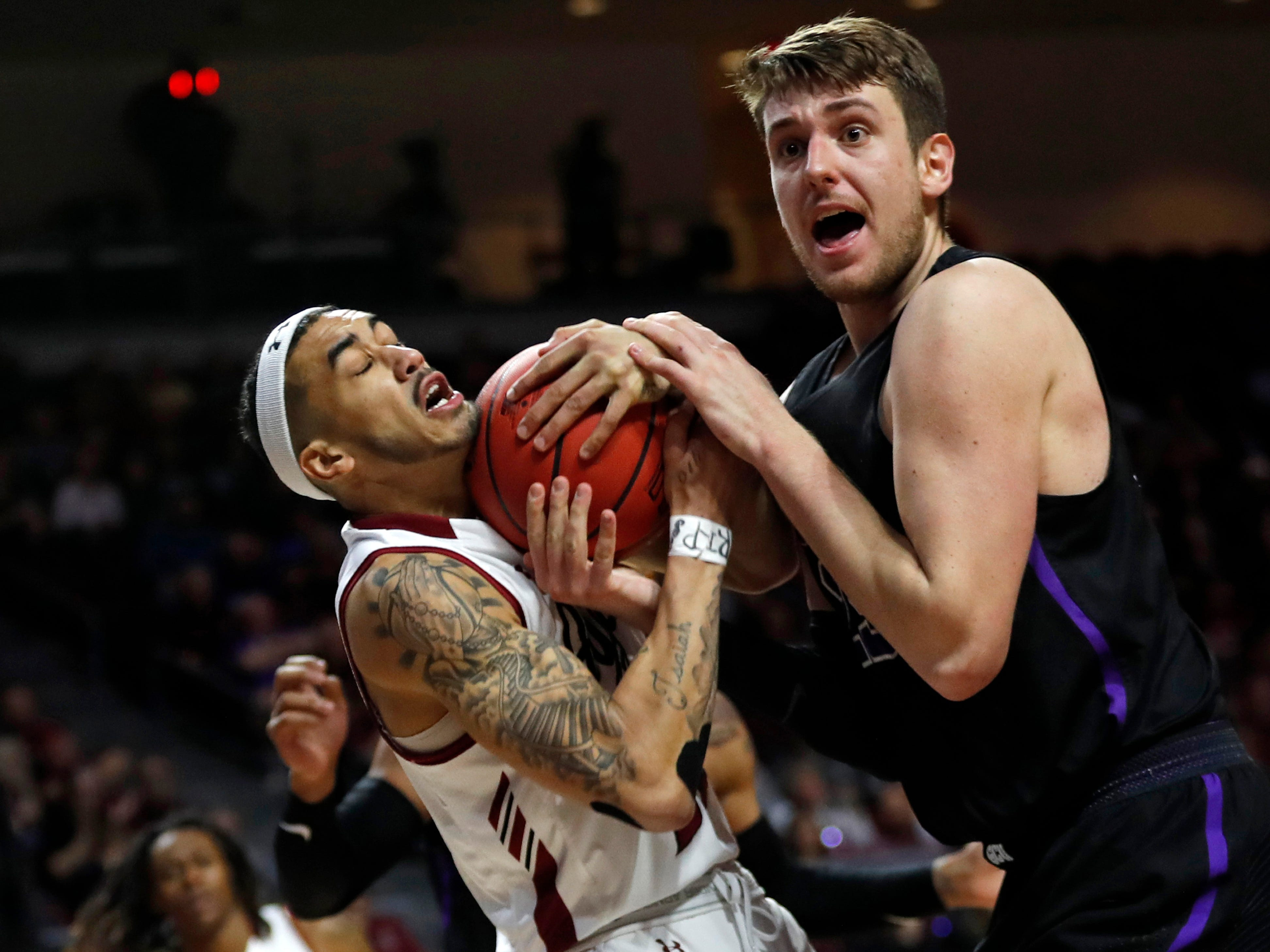 New Mexico State guard Trevelin Queen (20) and Grand Canyon's Alessandro Lever vie for a rebound during the first half of an NCAA college basketball game for the Western Athletic Conference men's tournament championship Saturday, March 16, 2019, in Las Vegas.