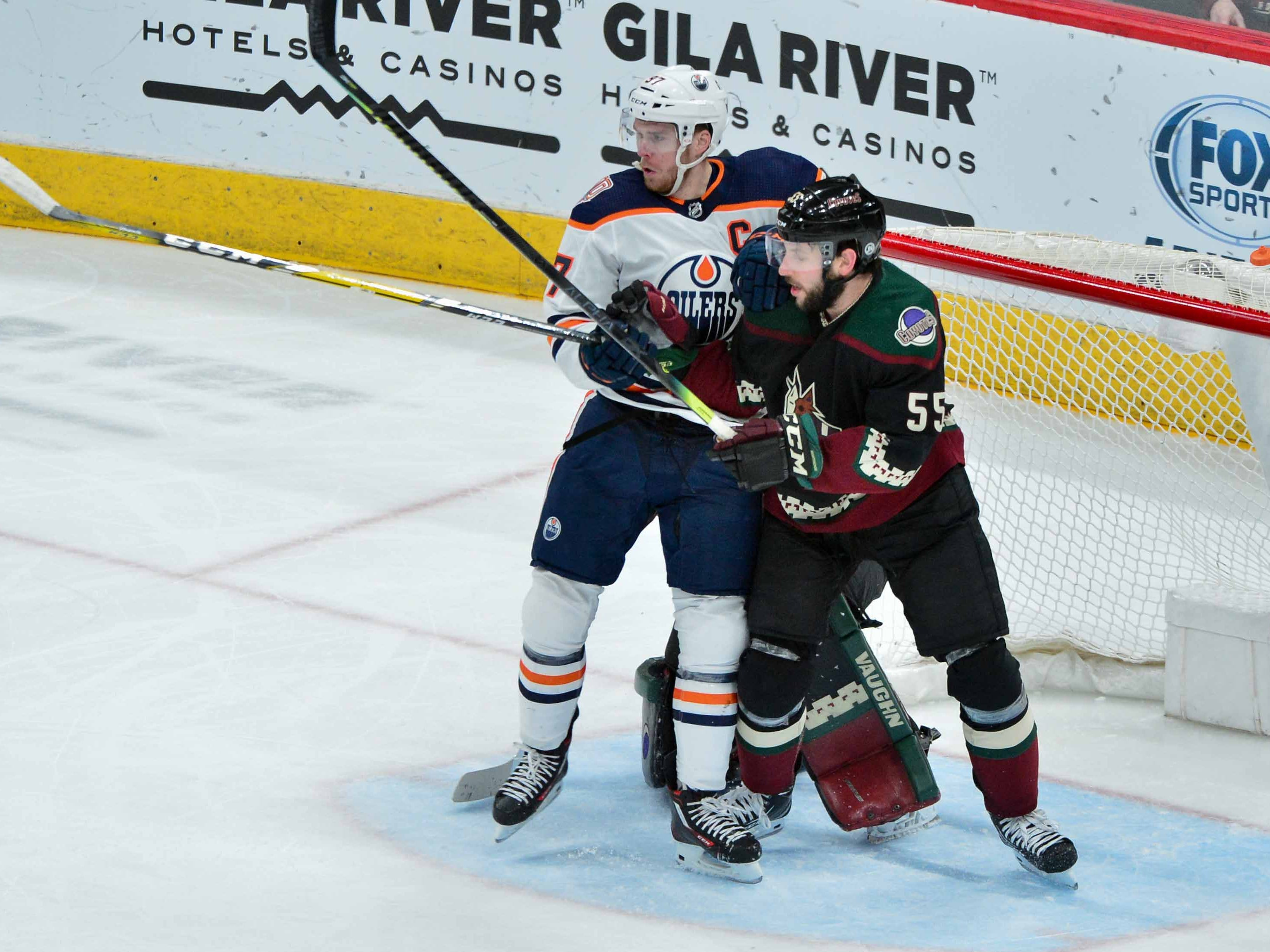Mar 16, 2019; Glendale, AZ, USA; Edmonton Oilers center Connor McDavid (97) and Arizona Coyotes defenseman Jason Demers (55) battle for position in front of the net during the second period at Gila River Arena.