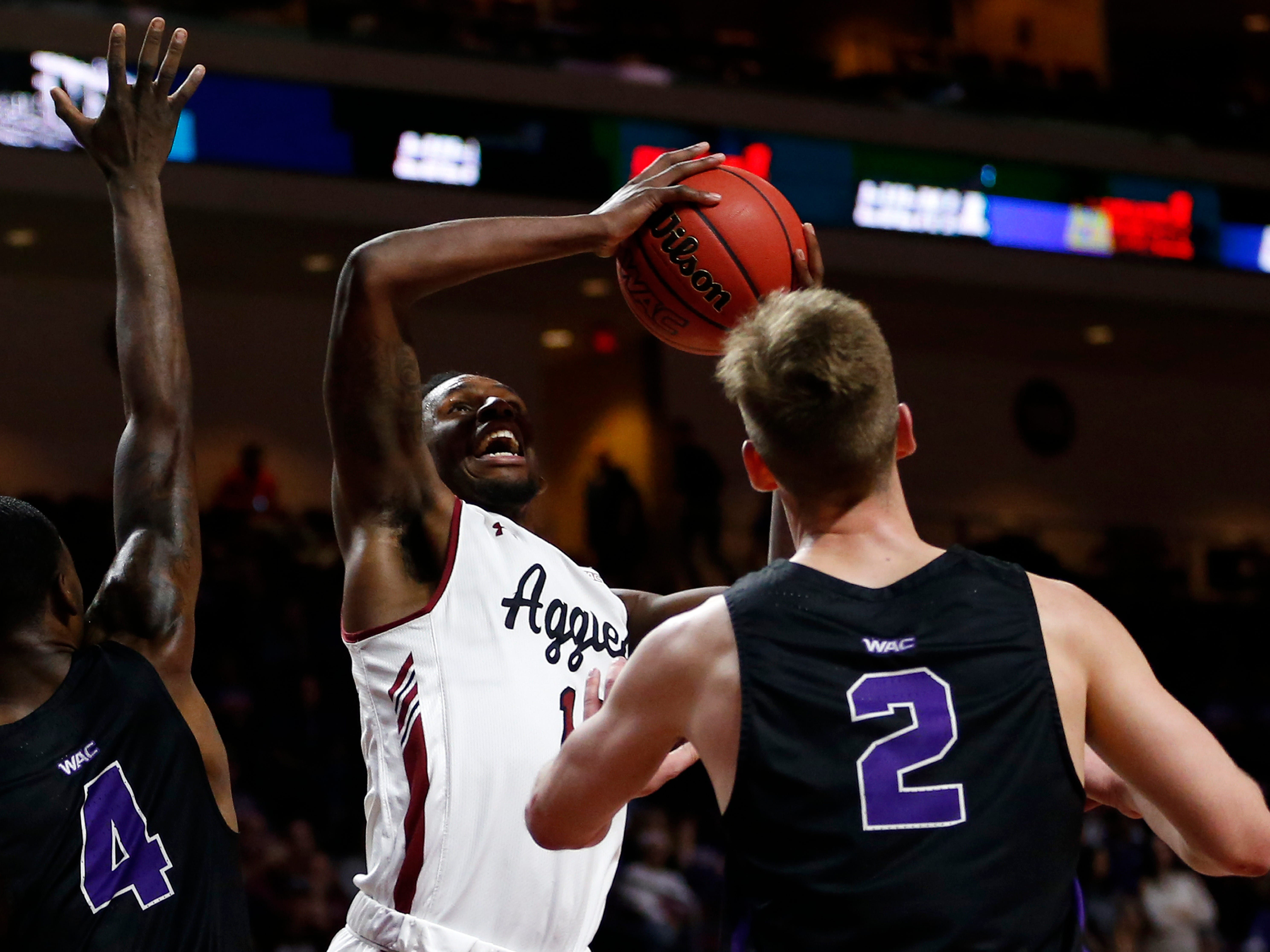 New Mexico State forward C.J. Bobbitt (13) puts up the ball between Grand Canyon's Oscar Frayer (4) and Trey Drechsel (4) during an NCAA college basketball game for the Western Athletic Conference men's tournament championship Saturday, March 16, 2019, in Las Vegas. New Mexico State beat Grand Canyon 89-57.