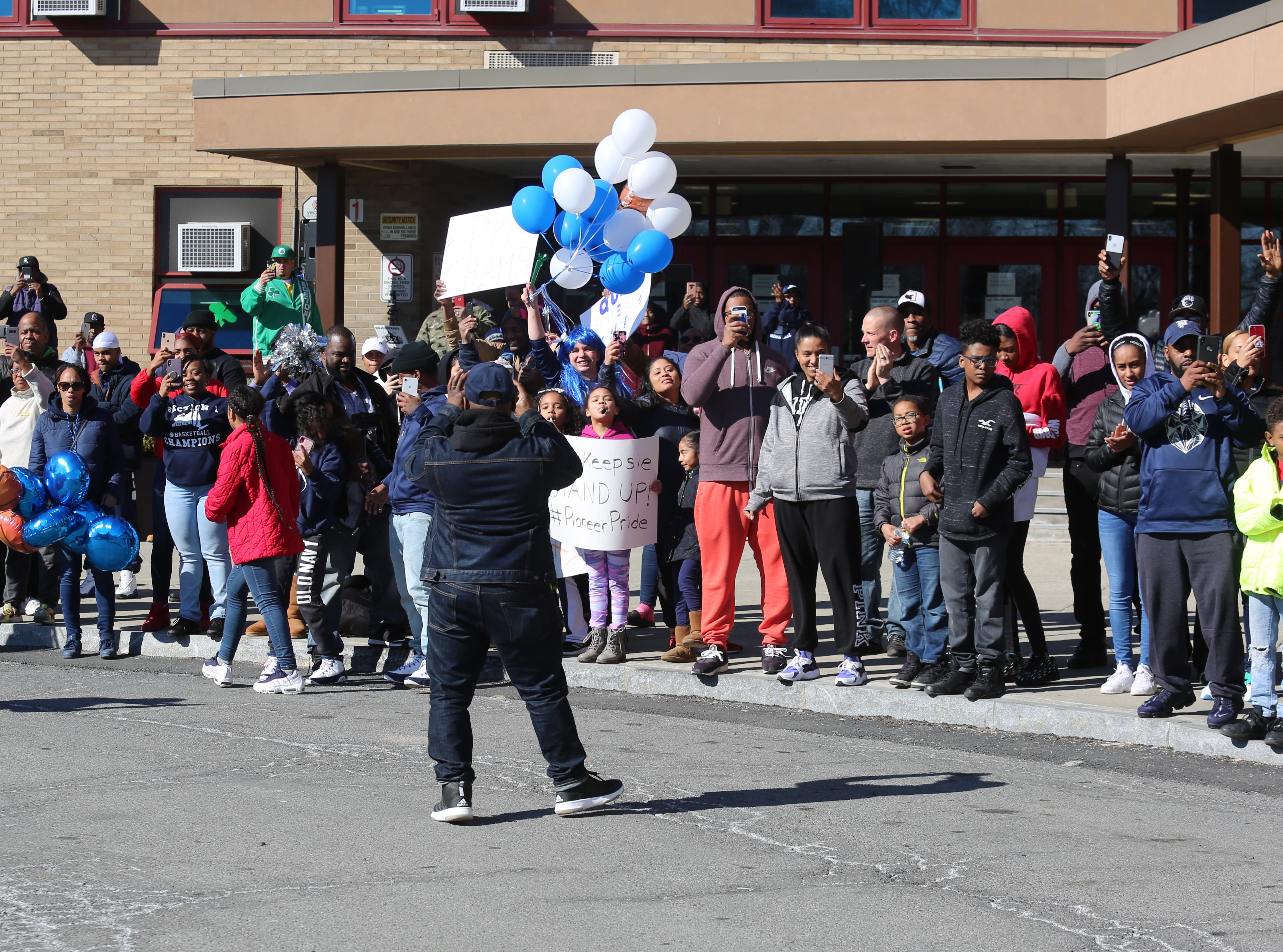 Poughkeepsie residents gathered in front of the high school on Sunday to greet the boys basketball team, returning from Binghamton with its first state championship since 1995.