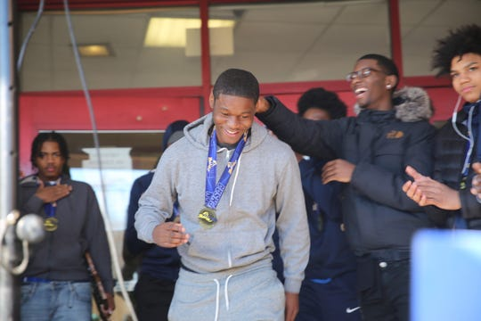 Jamik Carter smiles during a celebration at Poughkeepsie High School after the boys basketball team captured a state championship on Saturday.