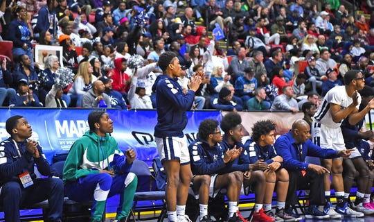 Marvin Lunsford (second from left) cheers on the Poughkeepsie boys basketball team during its win over Mendon in the state final on March 16.